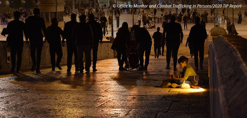 Photo credit: A boy sits on the ground on a bridge as a crowd of silhouetted people walks by him. Office to Monitor and Combat Trafficking in Persons/2020 TIP Report.