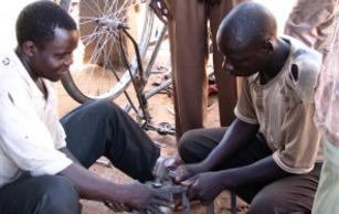 A Ugandan youth working on a bicycle