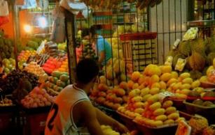A Filipino micro entrepreneur works at his fruit stand