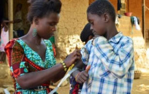 A Zambian health worker administers medicine