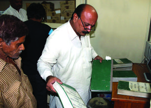 A tax collector reviews documentation from a citizen in Punjab, Pakistan