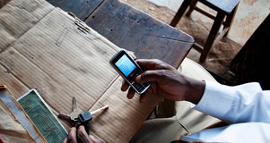 Person in Uganda holding a mobile phone above a table. Credit: Will Boase.