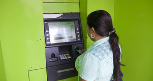 A woman uses a ATM cash machine in Baranoa, Colombia.