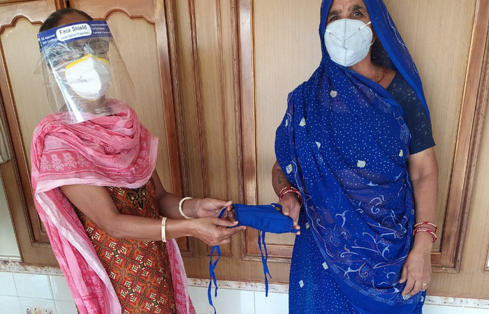 A woman in India wearing a face mask and face shield handing a cloth face mask to another woman also wearing a face mask