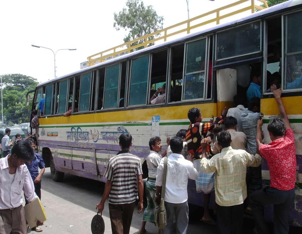 Migrants board a bus in Bangladesh